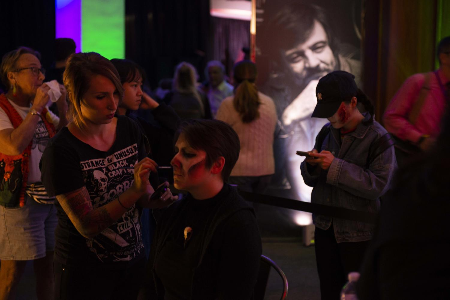 Visitors at Living with the Dead: A Party Celebrating the George A. Romero Archival receive makeup courtesy of ScareHouse.
