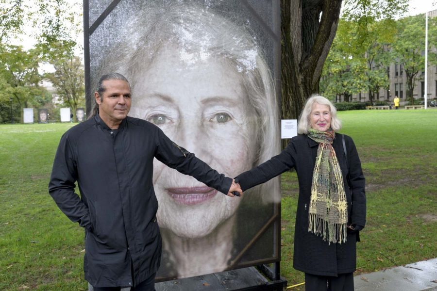"Luigi Toscano (left), creator of the ""Lest We Forget"" exhibit, holds hands with Solange Lebovitz (right), a Holocaust survivor, on Wednesday outside the Cathedral of Learning."