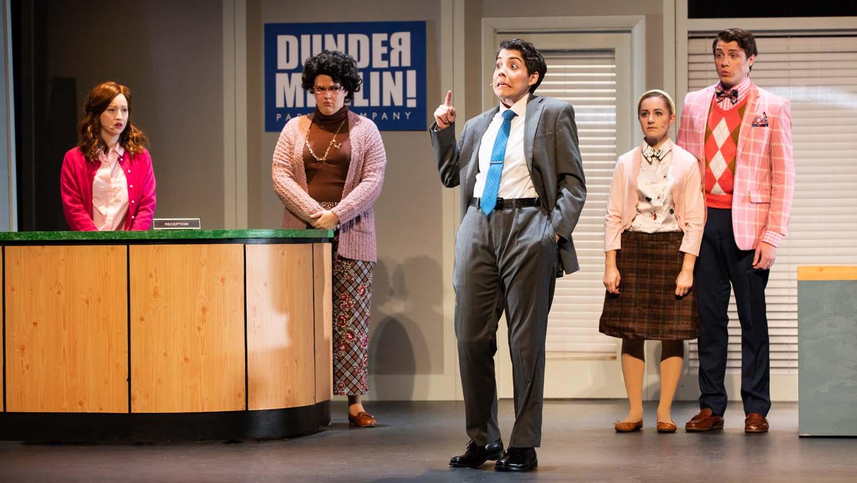 "Actress Emma Brock (center) stars as Michael Scott in ""The Office! A Musical Parody."""