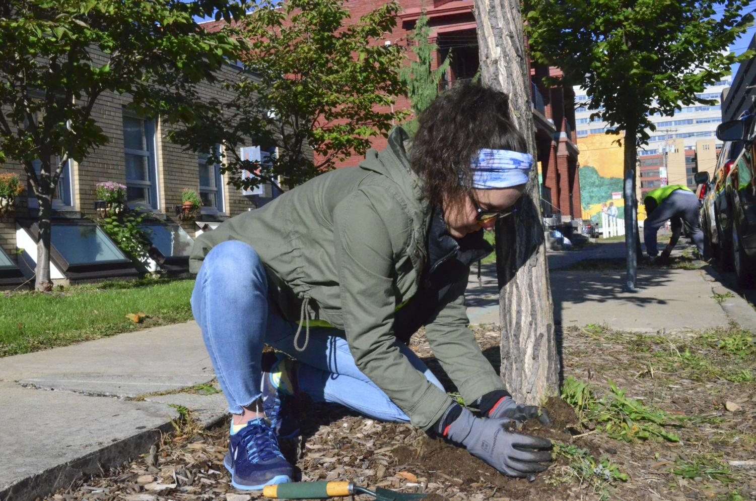 Junior nursing major Ashley Van Slyke helps with landscaping outside the Oakland Career Center as a part of Pitt Make a Difference Day on Saturday.