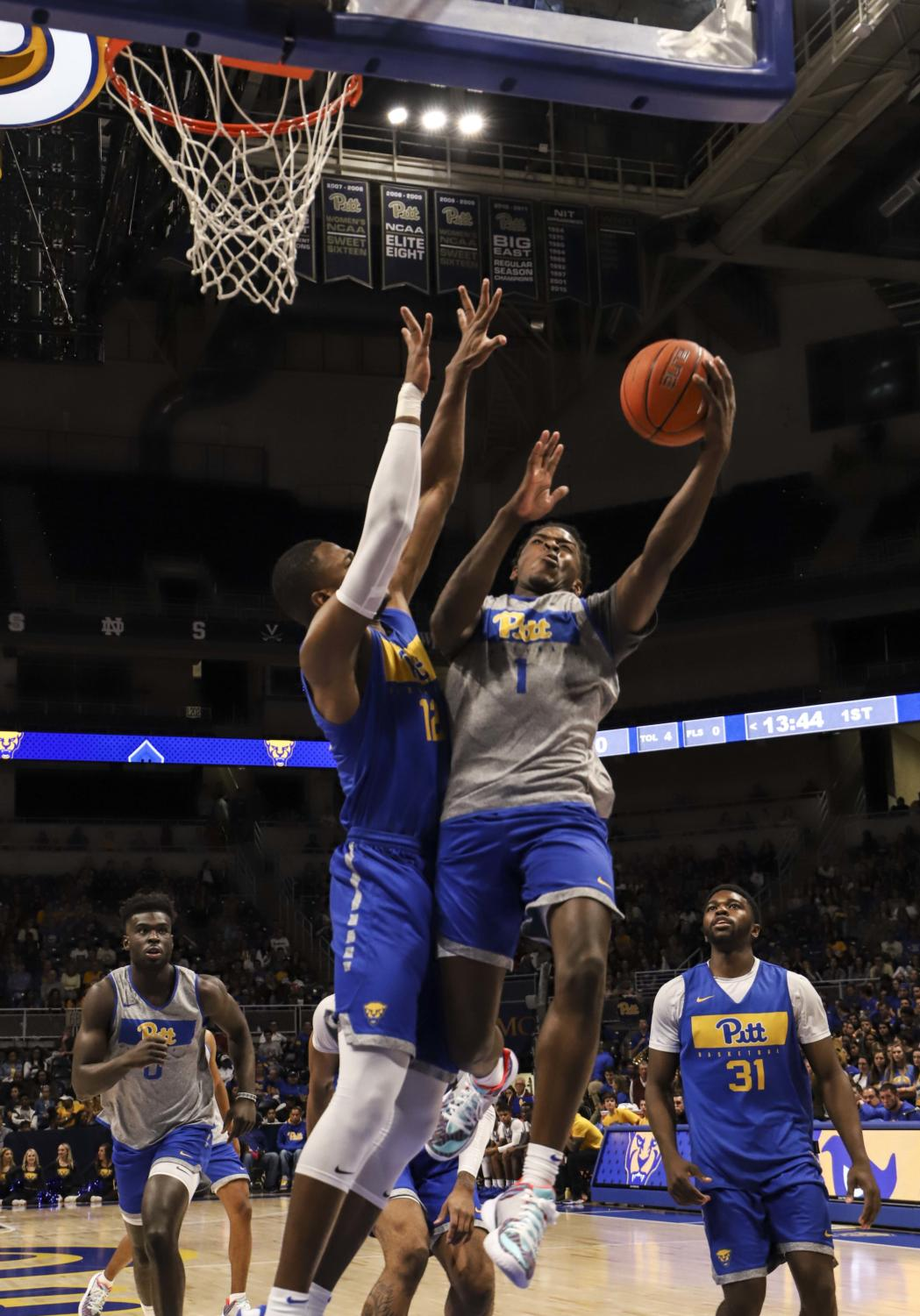 First-year forward Karim Coulibaly (12) contests a layup by sophomore guard Xavier Johnson (1).