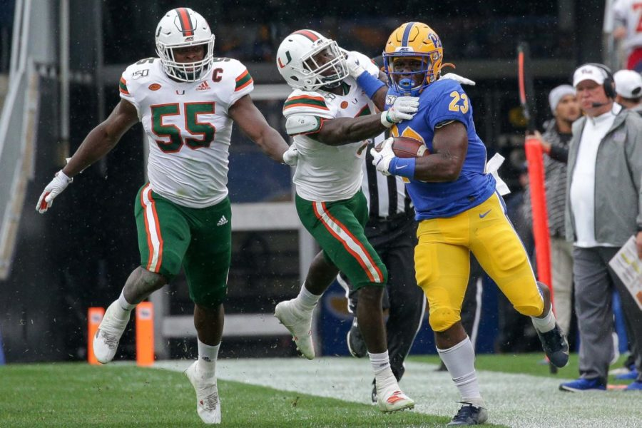 Redshirt sophomore Todd Sibley Jr. (23) stiff-arms Miami sophomore safety Amari Carter (05) to fight for extra yards before being shoved out of bounds.