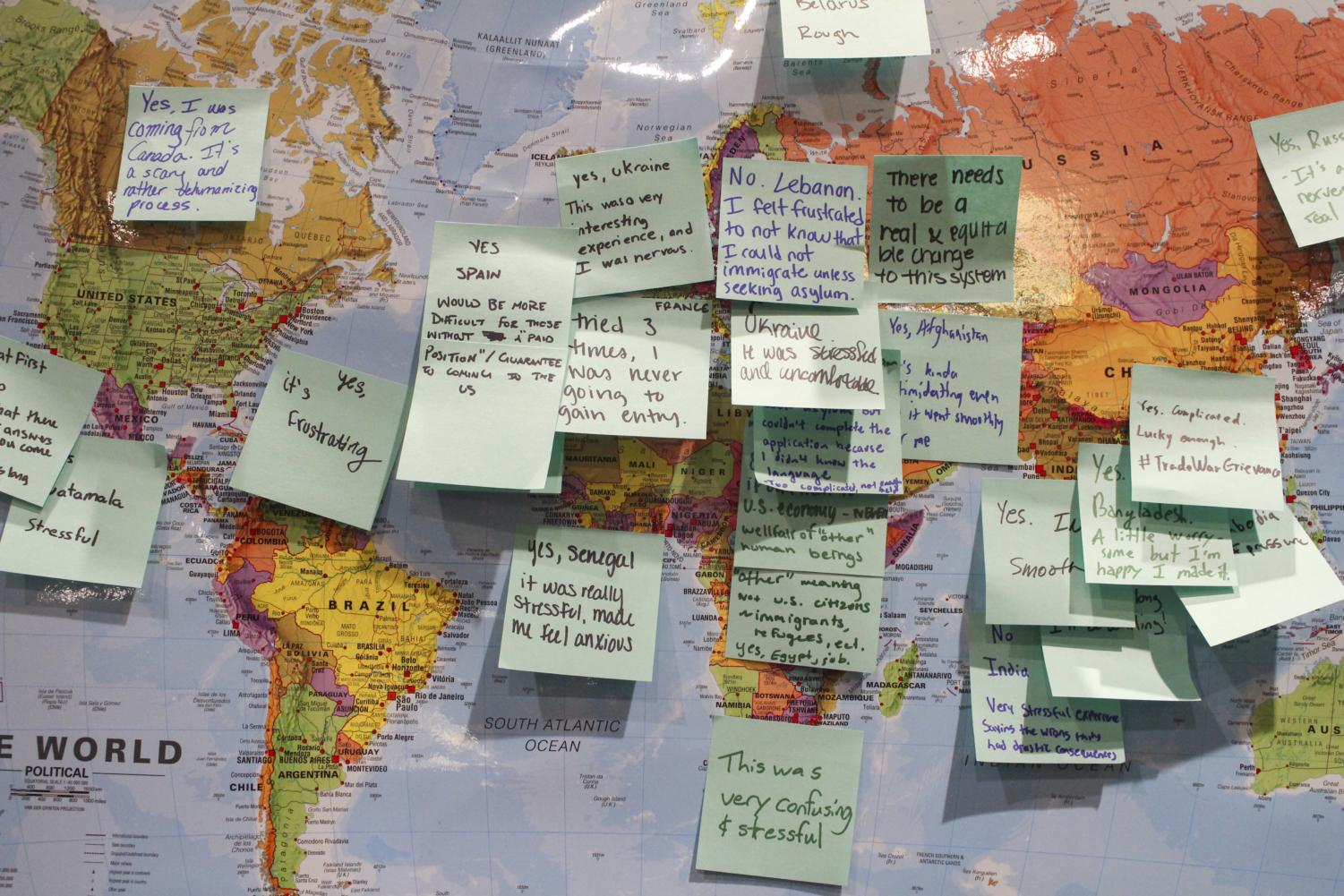 Students described their experiences on sticky notes with a mock immigration process based on which country they were assigned in the activity.