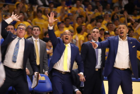 Head coach Jeff Capel (far right) and his coaching staff frantically signal to Pitt's players during a game.