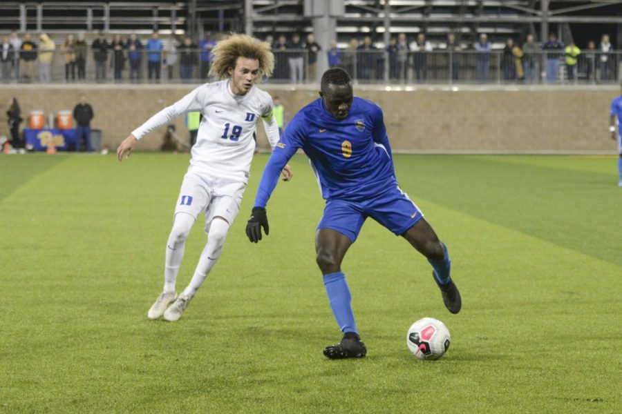 Edward Kizza (9) maneuvers around Duke's Brandon Williamson (19). On Thursday night, Pitt men's soccer will play in the NCAA tournament for the first time in 54 years.