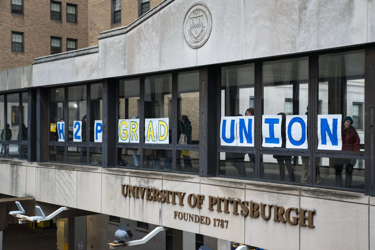 Grad union organizers hold signs against the windows of the Forbes Avenue sky bridge on Wednesday afternoon.