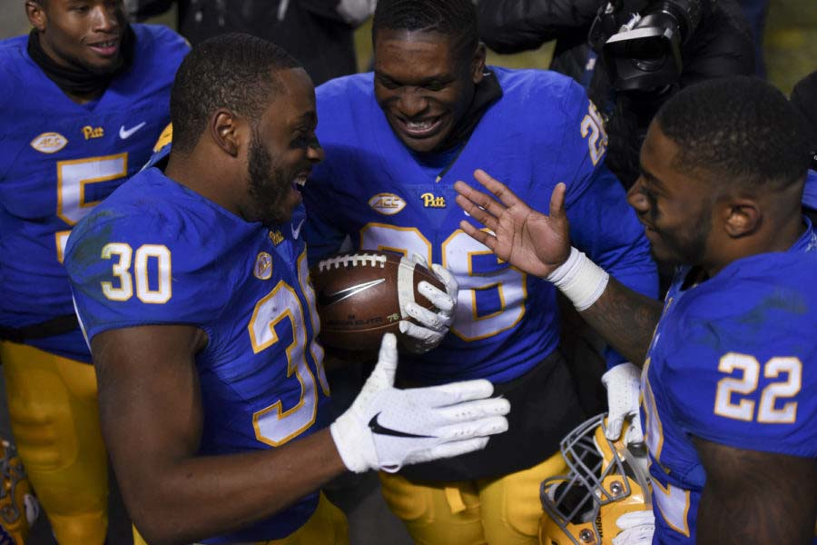 Then-seniors Qadree Ollison (30) and Darrin Hall (22) shake hands after Hall surprises Ollison with a game ball on Senior Day — a celebration of the seniors at their last home game — after the Panthers defeated the Hokies Saturday.