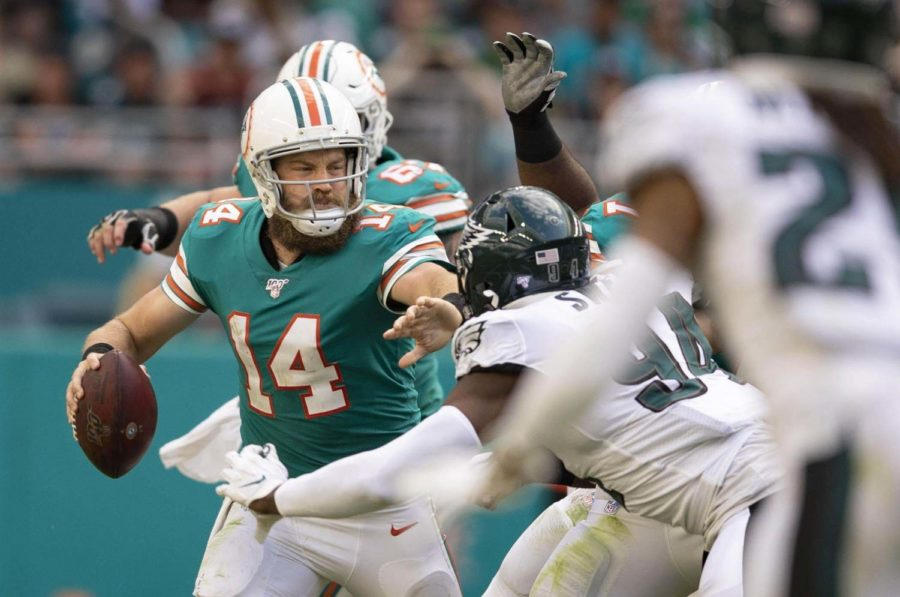 Dolphins quarterback Ryan Fitzpatrick fights off Eagles defenders in the third quarter. The Eagles were called for roughing the passer on the play.