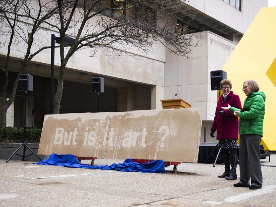 """Provost Ann Cudd and Assistant Provost Nancy Tannery stand next to a board that displayed the words """"But is it art?"""" after having water poured on it."""