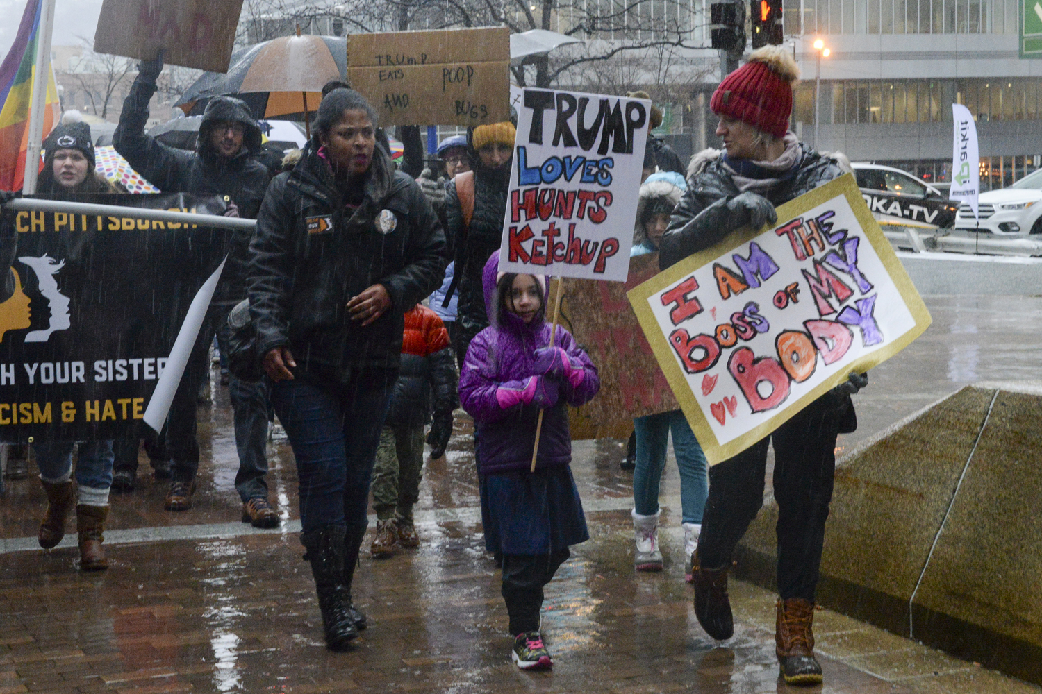 Demonstrators at the fourth annual Pittsburgh Women's March walk through the rain on Saturday.