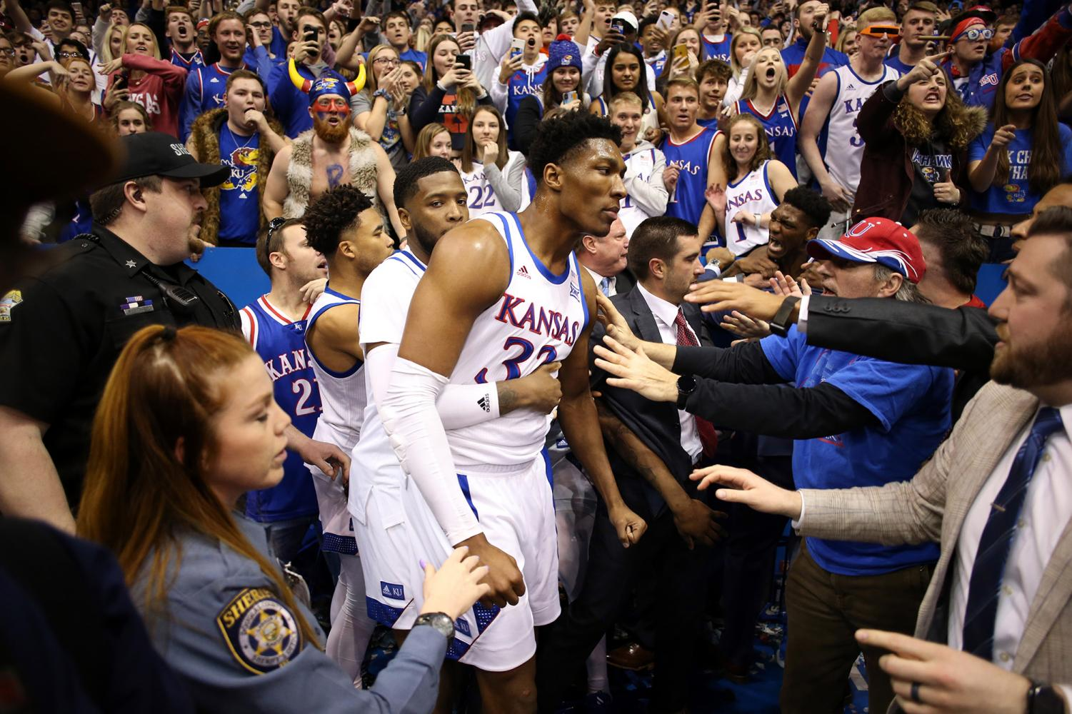 Kansas' David McCormack (33) is held back by teammate Isaiah Moss during a brawl following a game against rival Kansas State at Allen Fieldhouse in Lawrence, Kansas, on Tuesday. Kansas won, 81-60.