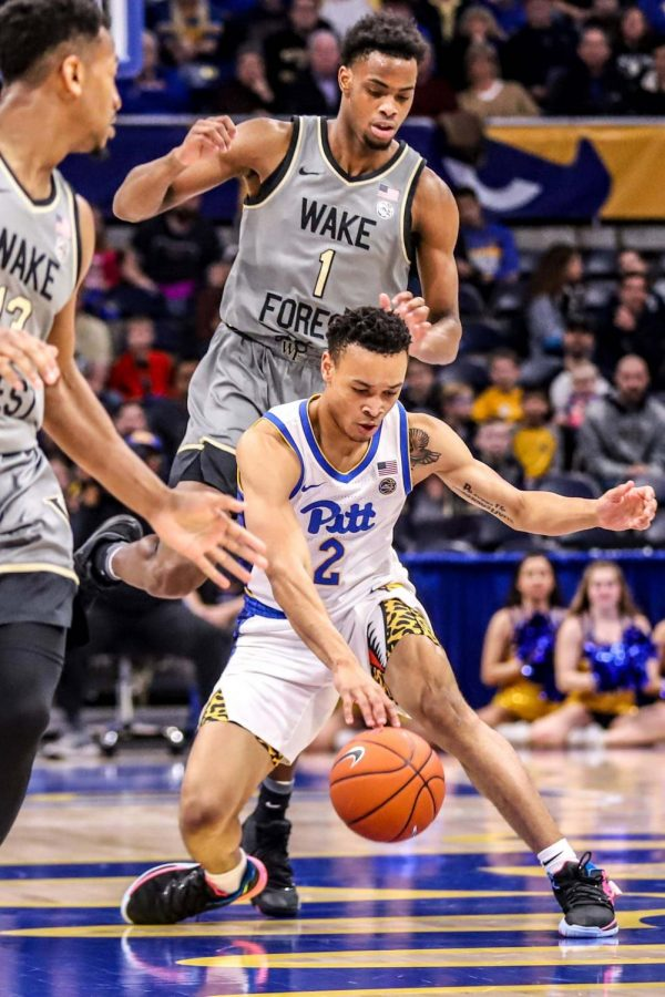 Sophomore guard Trey McGowens (2) maneuvers the ball between Wake Forest's Andrien White and Isaiah Mucius.