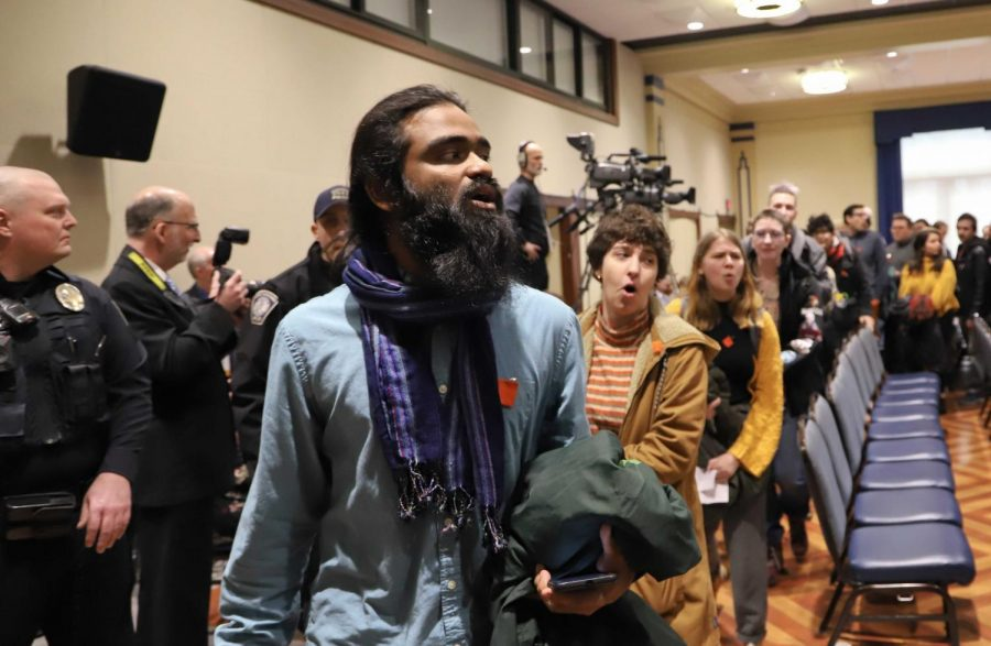 Around 100 students protested in favor of fossil fuel divestment at Friday morning's Board of Trustees meeting.