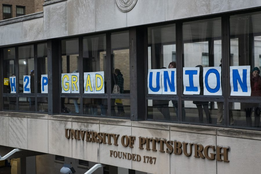 Grad+union+organizers+hold+signs+against+the+windows+of+the+Forbes+Avenue+sky+bridge+during+a+demonstration+in+December.%0A