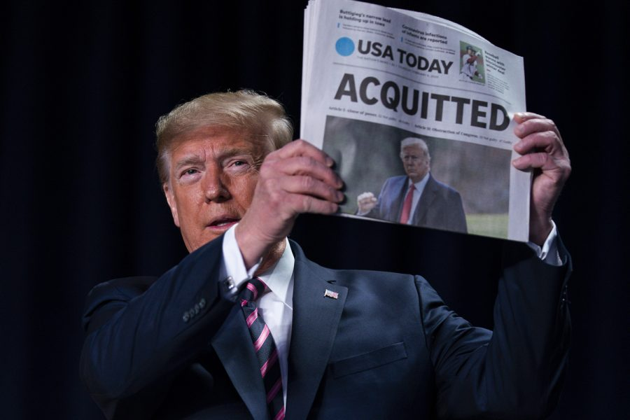 President Trump holds up a newspaper with the headline that reads