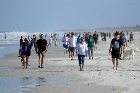 People are seen at the beach on April 17 in Jacksonville Beach, Florida, after social distancing restrictions were partially eased.
