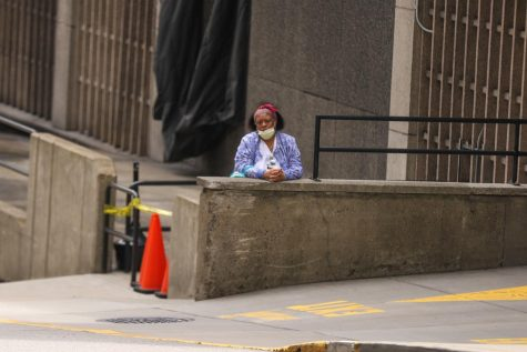 A hospital worker awaits a shuttle outside the UPMC Presbyterian parking garage.