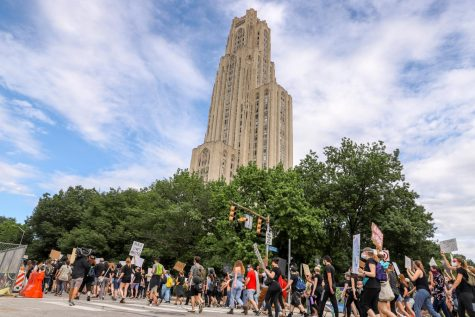 Protesters march down Fifth Avenue in the shadow of the Cathedral of Learning at a protest on Saturday.