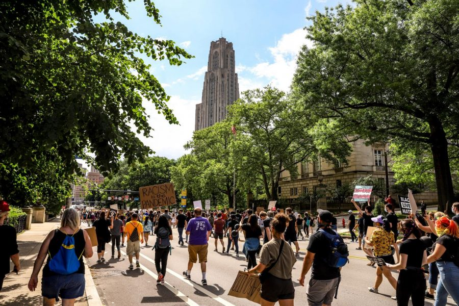 Protesters march down Forbes Avenue, in the shadow of the Cathedral of Learning, at a Saturday protest.