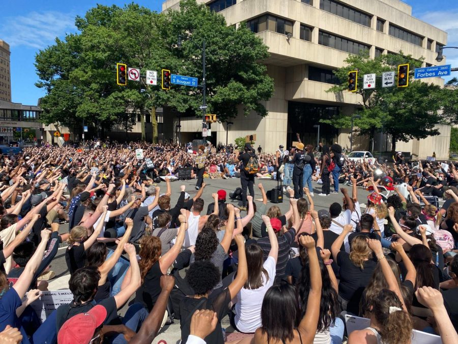 Hundreds of Black Lives Matter protesters raise their fists in solidarity at the intersection of Forbes Avenue and South Bouquet Street on June 13.