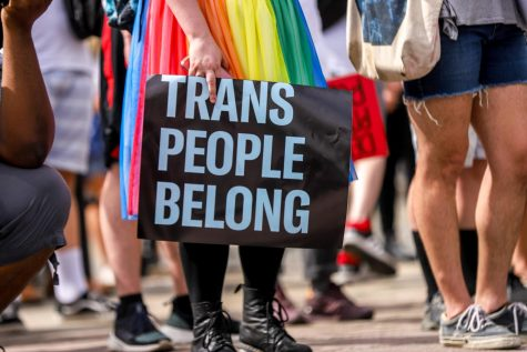 "A protester holds a ""Trans People Belong"" sign during a June protest for Black trans lives."