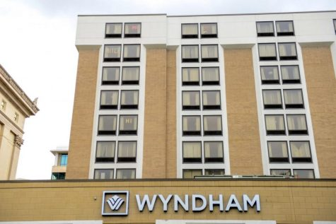 Students write messages with sticky notes in the windows of their Wyndham hotel dorm rooms.
