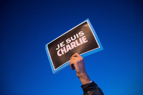 "A man raises a ""Je Suis Charlie"" — translation: ""I am Charlie"" — sign during a rally in support of Charlie Hebdo on Jan. 7, 2015, in Marseille, France."