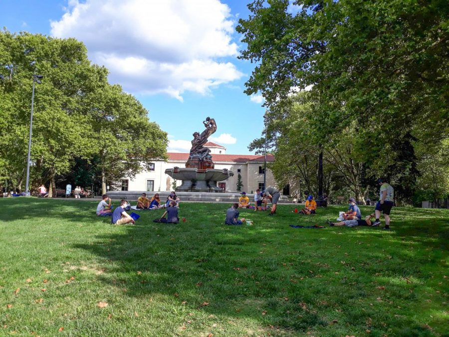 Students gather on the lawn outside of the Frick Fine Arts building.