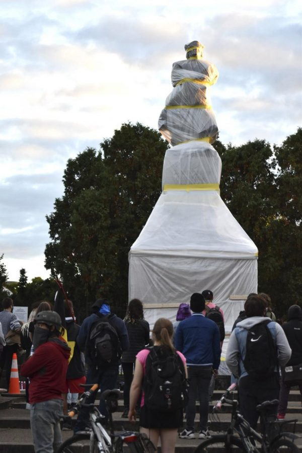 Protesters gather at the Columbus statue, now covered, Monday evening.