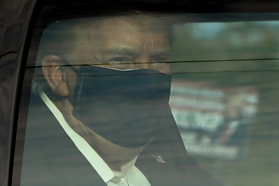 President Donald Trump wears a protective face mask in a motorcade outside Walter Reed National Military Medical Center during his treatment for COVID-19 on Sunday in Bethesda, Maryland.