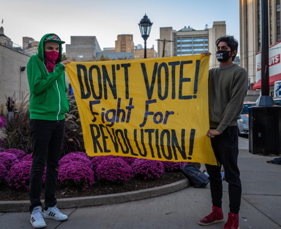 "Six members from Serve the People Pittsburgh gathered at the corner of S. Bouquet Street and Forbes Avenue urging pedestrians to not vote and instead focus on ""revolutionary solutions"" Tuesday afternoon."