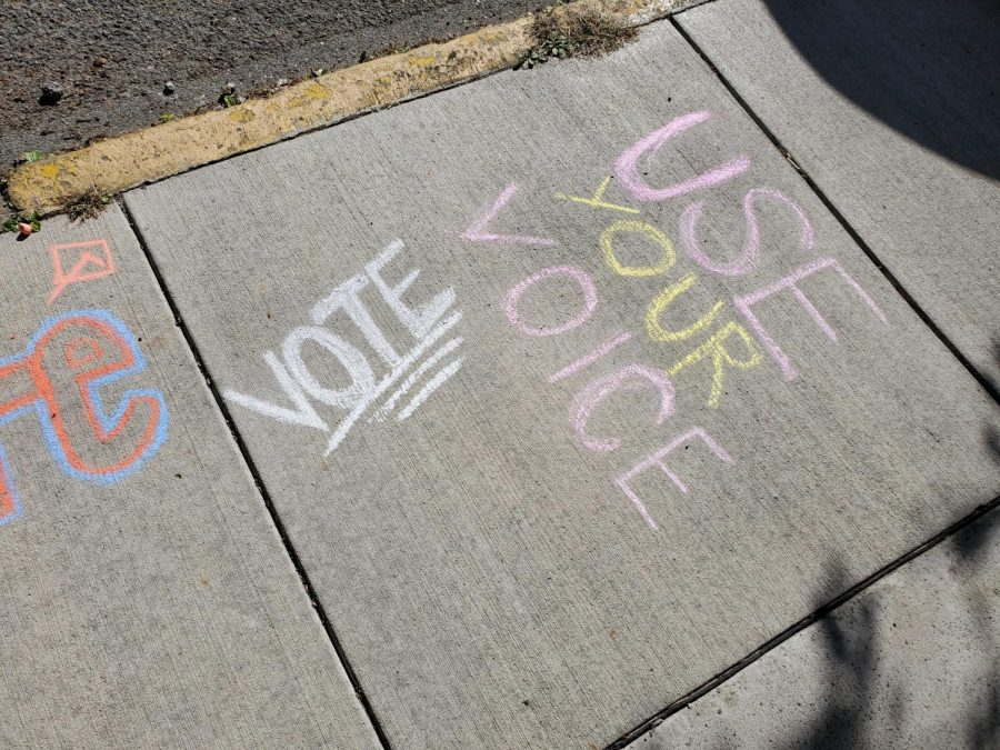 Chalk art on the sidewalk outside the McKee Place fire station urges people to vote.
