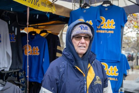 Chas Bonasorte, owner of The Pittsburgh Stop on the corner of Forbes Avenue and Bigelow Boulevard, stands in front of his apparel and merchandise stand.