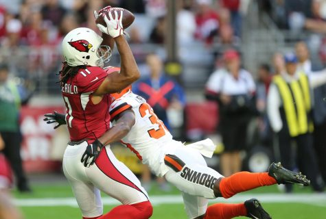 Arizona Cardinals wide receiver Larry Fitzgerald hauls in a first-down reception as he is hit by Cleveland Browns defensive back T.J. Carrie in the first quarter, Dec. 15, 2019, at State Farm Stadium.