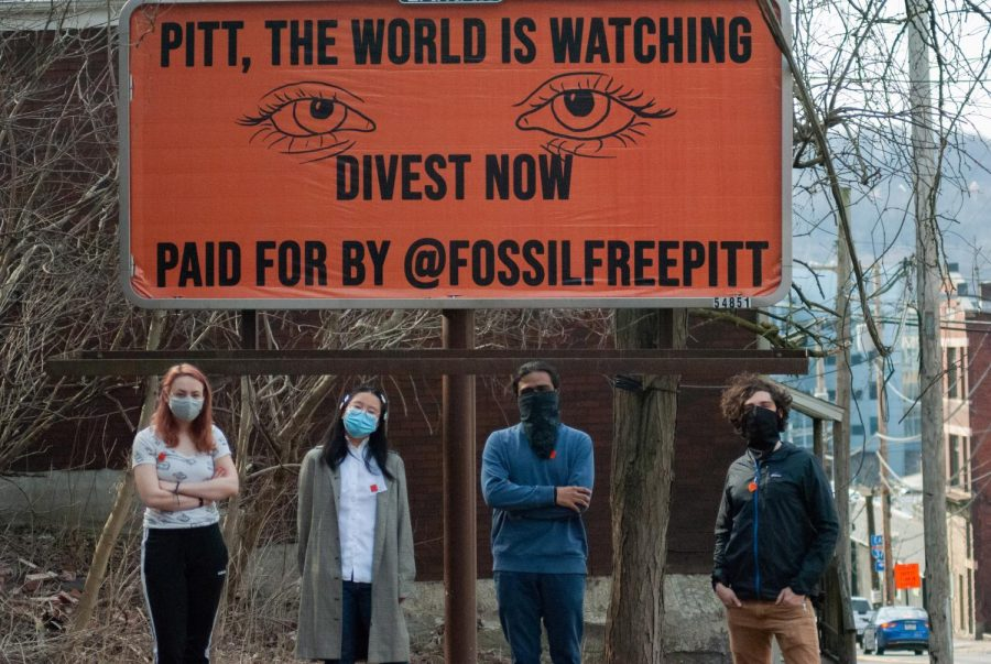 Fossil Free Pitt Coalition organizers (left to right) Kelly McQueston, Elina Zhang, Abishek Viswanathan and Nick Suarez stand in front of the coalition's billboard off Boulevard of the Allies.