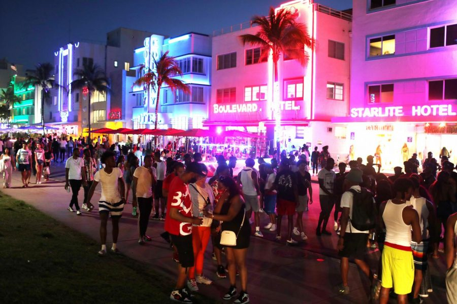 People enjoy themselves as they walk along Ocean Drive on March 18 in Miami Beach, Florida. College students have arrived in the South Florida area for the annual spring break ritual.