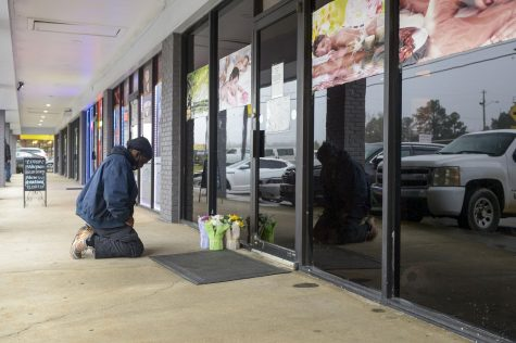Acworth resident Derrick Franklin places flowers near the entrance of Youngs Asian Massage Parlor Wednesday, March 17, 2021 in Cherokee County, Georgia.