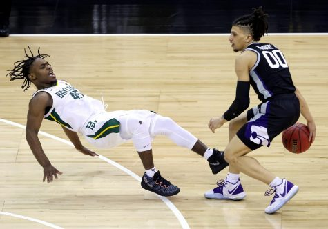 Mike McGuirl (00) of the Kansas State Wildcats controls the ball as Davion Mitchell (45) of the Baylor Bears defends during the quarterfinal game of the Big 12 basketball tournament at the T-Mobile Center on March 11 in Kansas City, Missouri.