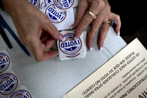 "A poll worker gets ""I Voted"" stickers ready to hand to voters as they finish up at the ballot booths."
