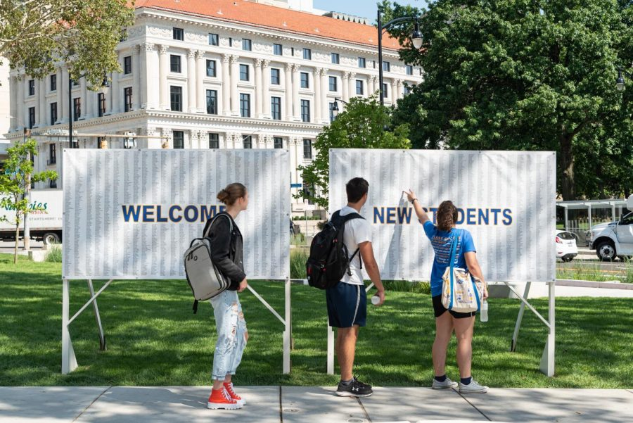 Three students read the sign where Pitt greets its largest incoming class ever this year — a total of 5,195 students.