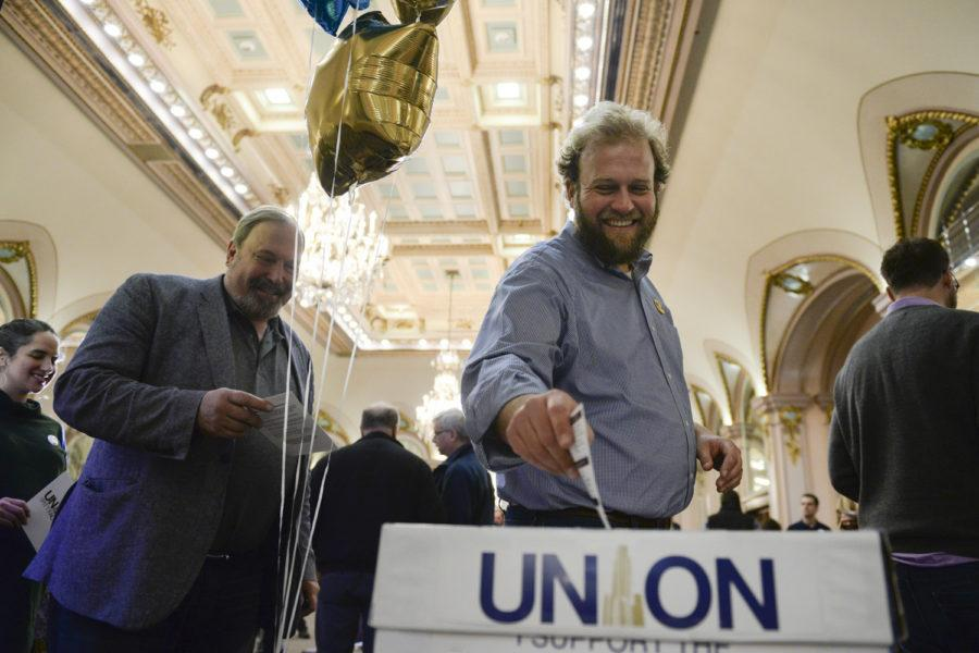 Tyler Bickford, a professor in the English department, drops one of the first union cards at a kickoff event held by Pitt faculty union organizers in the William Pitt Union Ballroom in January 2018.