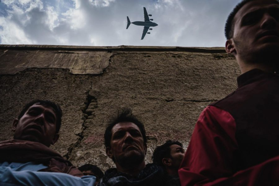 A plane flies overhead a group of people gathered around the remains of a car hit by an American drone strike in Kabul, Afghanistan.