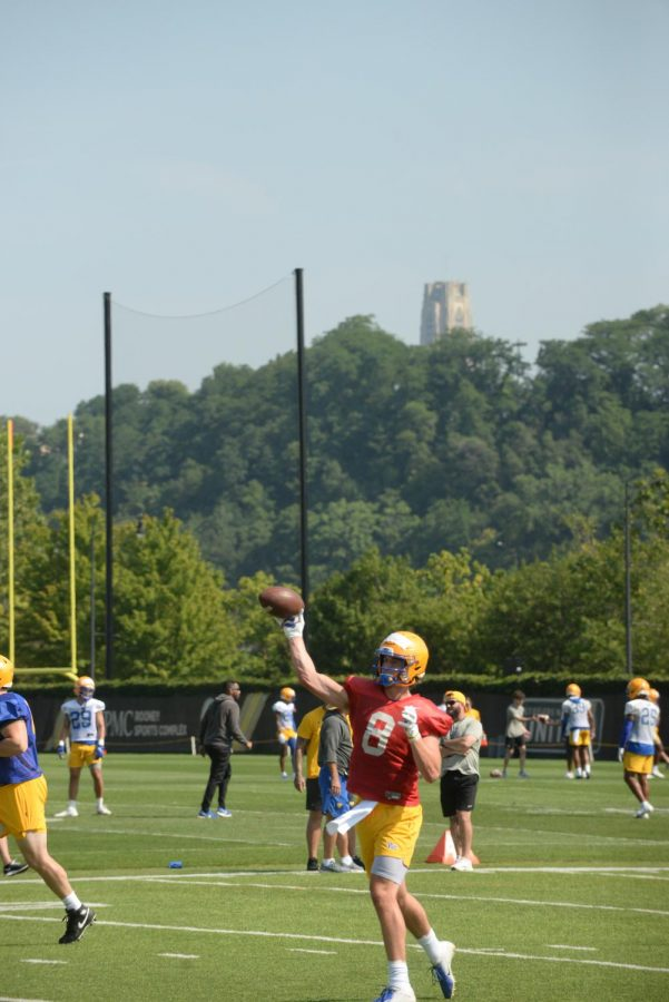 Kenny Pickett, the super-senior quarterback, throws the ball with the Cathedral of Learning in the background.