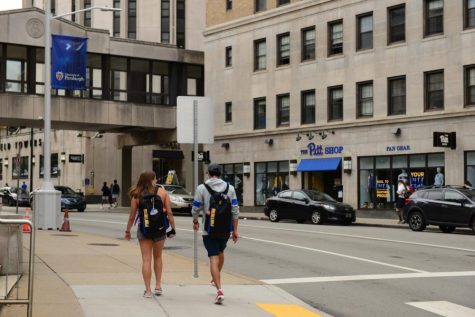 Two students walk along the sidewalk adjacent to David Lawrence Hall.