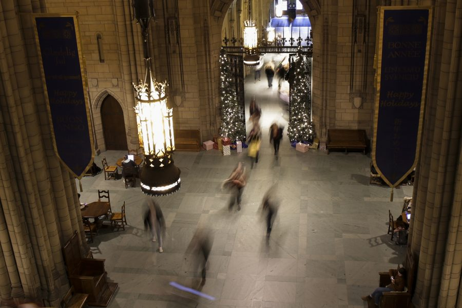 Students walk on a spring 2020 day through the Cathedral of Learning to classes.