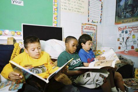 Three boys reading in a classroom.