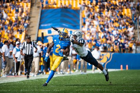 A UNH football player attempts to tackle sophomore running back Israel Abanikanda during the Pitt vs. UNH game in September.