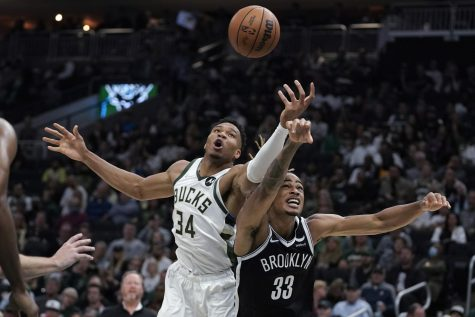 Milwaukee Bucks Giannis Antetokounmpo (34) and Brooklyn Nets Nicolas Claxton (33) reach for the ball at Fiserv Forum in Milwaukee on Tuesday.