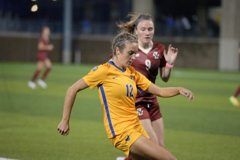Pitt's Anna Bout (12) fights for possession of the ball against Boston College's Sam Smith (9) at Ambrose Urbanic Field on Thursday night.
